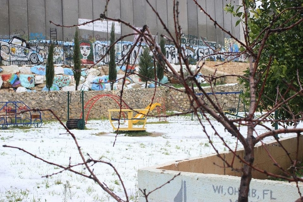 Snow carpets playground by the security wall in Bethlehem