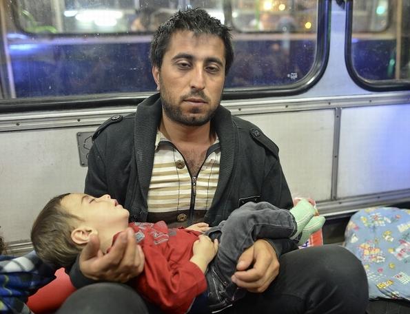 Exhaustion: refugee father and son in Budapest await bus to Austria (c) Art Widak/Demotix/Corbis