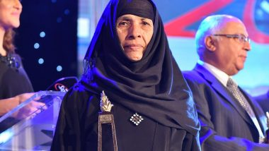 Widow in traditional black clothing holds her award