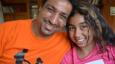 Portrait shot of father and daughter Hamid and Aya smiling