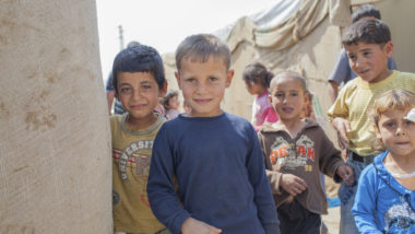 Young Syrian boys beside tents in a refugee camp
