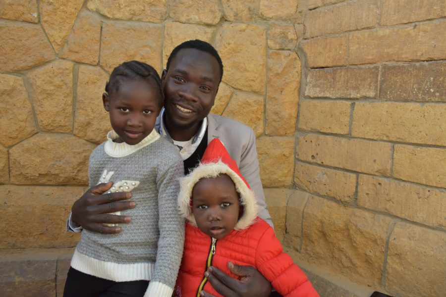 Sudanese teacher Michael Angelo with two of his children