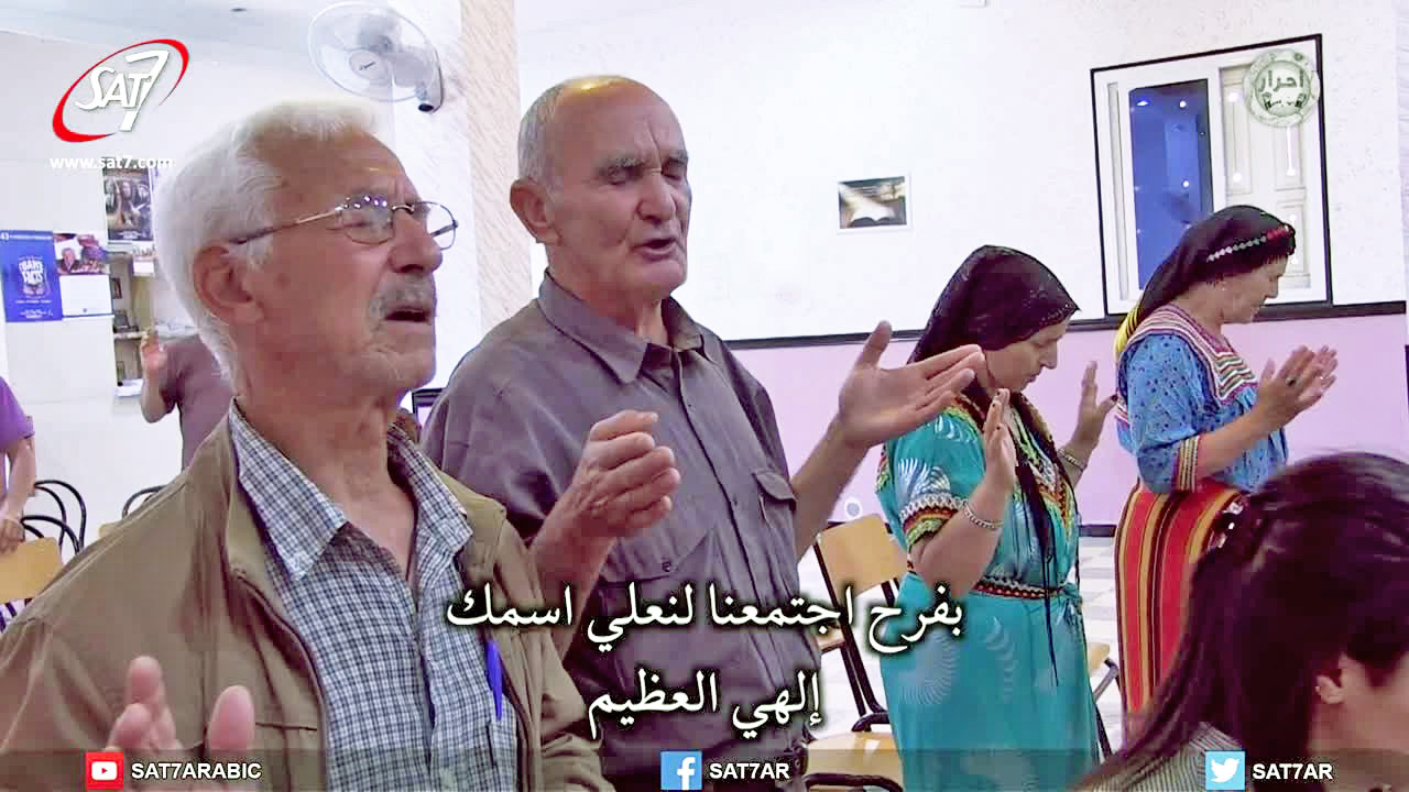 Amoqran (centre) worships at church