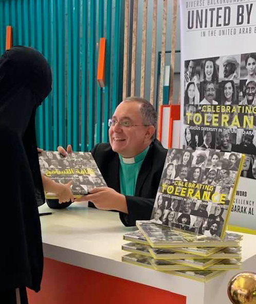 "Andrew wearing dog collar presents his book ""Celebrating Tolerance"" to a woman wearing a black abaya"