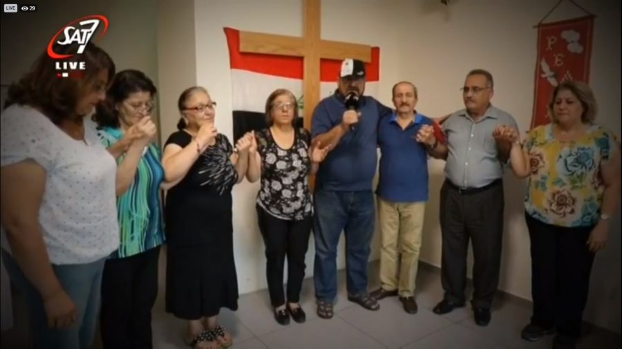 A group of Christians link hands in prayer while standing in front of a wooden cross