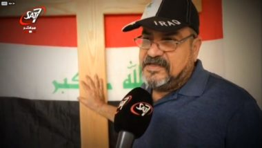 Man wearing baseball cap places hand on wooden cross in front of flag of Iraq