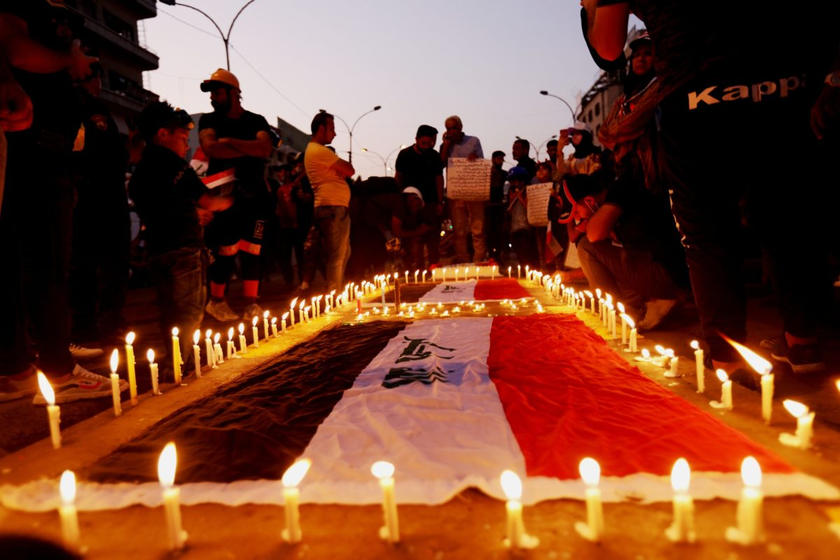People gathered around a candlelit flag as part of a peaceful demonstration