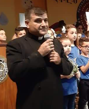 Father Bidoyan stood holding a microphone
