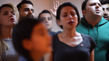 Seven young adult Iranian men and women with eyes closed in worship