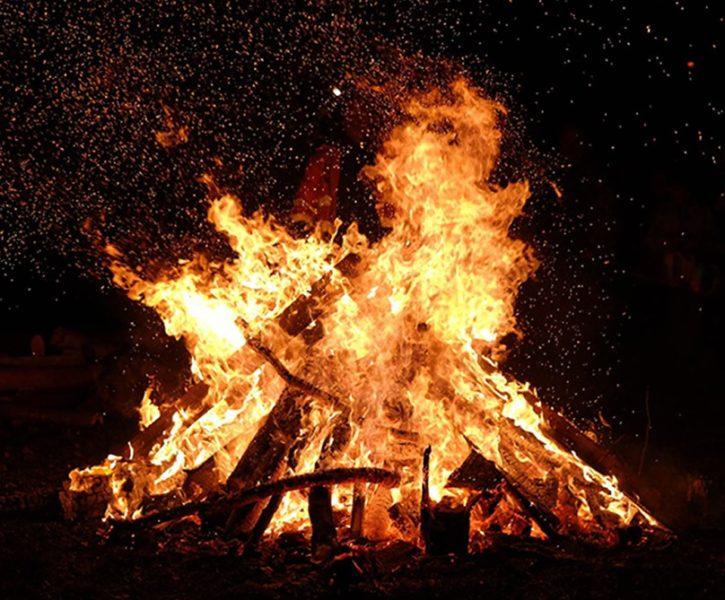 bonfire blazing against black sky