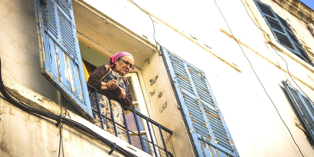 Elderly woman looking out of her balcony