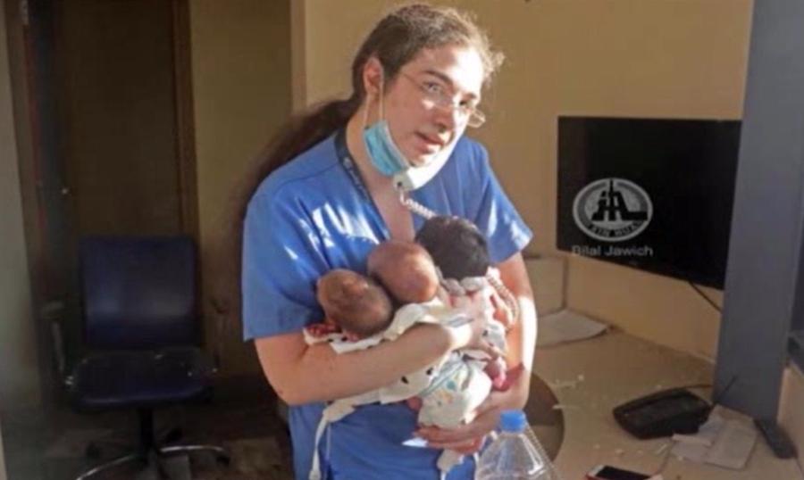 Female nurse holds three newborn babiesin her arms