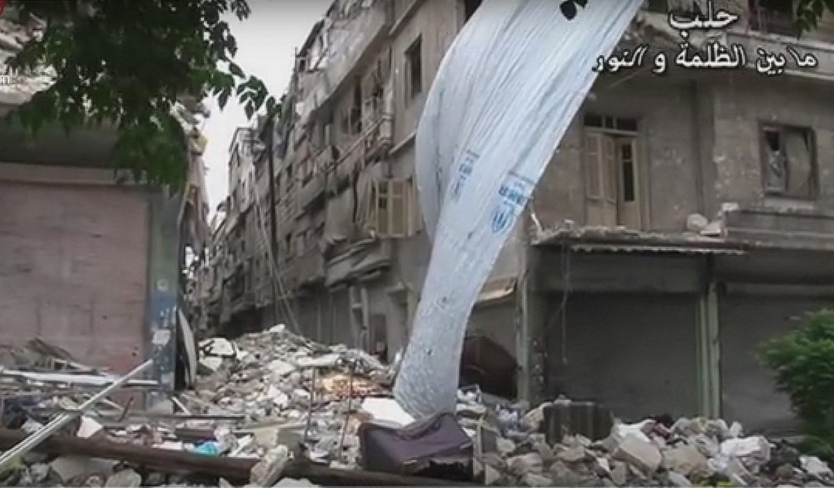 A UNHCR tarpaulin blows in the breeze in a scene of desolation in Aleppo, Syria.