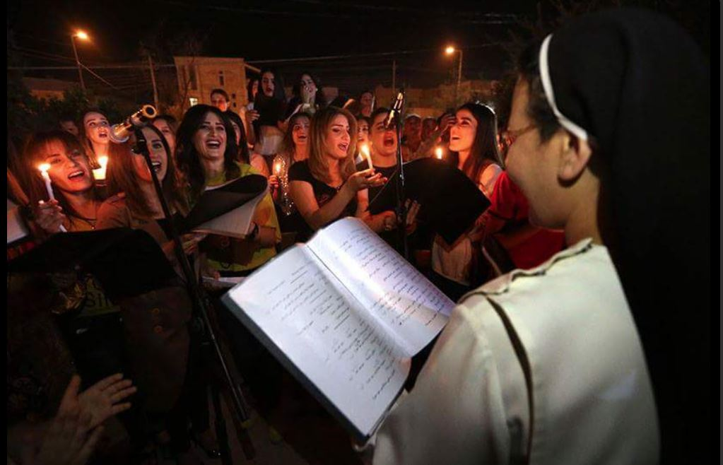 Nun leads singing in candlelit group