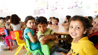 Class of primary age refugee children sit at round desks